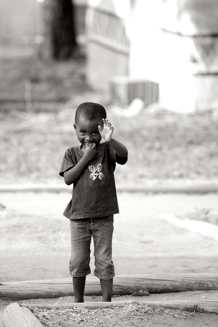 One of the children in the village waves as we walk by - Ryan Graham