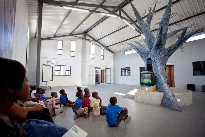 Young learners sit and watch a movie underneath the tree.  For many of these learners this is their only opportunity to embrace the skills, literacy and ideas that will help them to succeed in life.