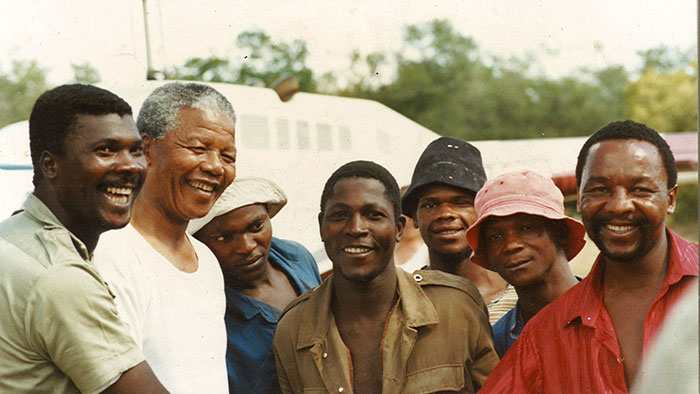 Nelson Mandela stands amongst Londolozi staff while visiting the lodge