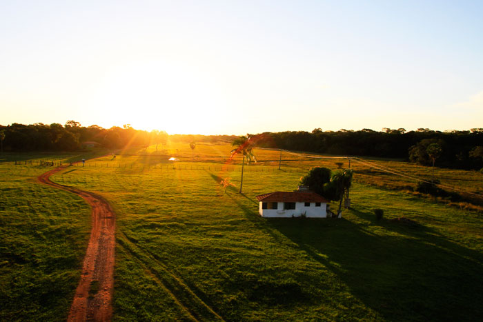 The sunsets over s small farm household in the Pantanal