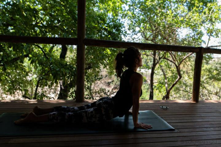 Londolozi's Yoga instructor, Sam Burnell, in upward facing dog position on the Londolozi Yoga Deck